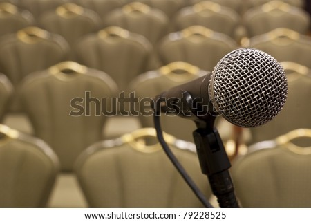 Microphone in front of several rows of empty chairs with shallow depth of field