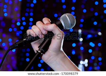 Microphone in hand singer on stage - stock photo