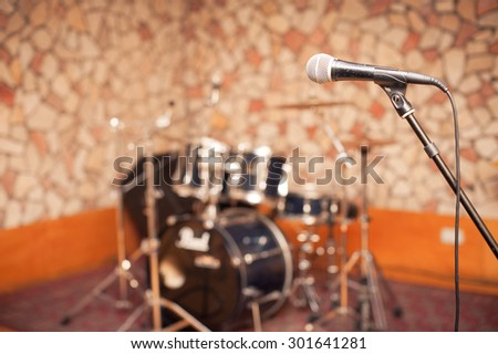 Microphone in music studio, stage with out of focus drums in background - stock photo