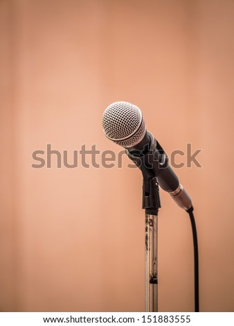 Microphone in spotlight isolated on orange curtain as background