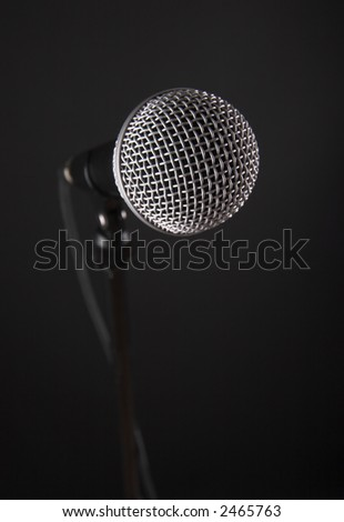Microphone on a stand, over black