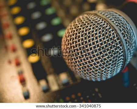 Microphone on amplifier equipment and out of focus background.: Vintage style and filtered process. - stock photo