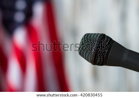 Microphone on blurred flag background. Microphone beside flag of America. Equipment is ready for speech. News for the nation.