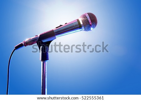 Microphone on microphone stand with cable and blue background. Front view. Horizontal composition.