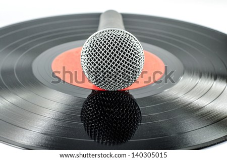 Microphone on old disc isolated on  white background - music concept -
