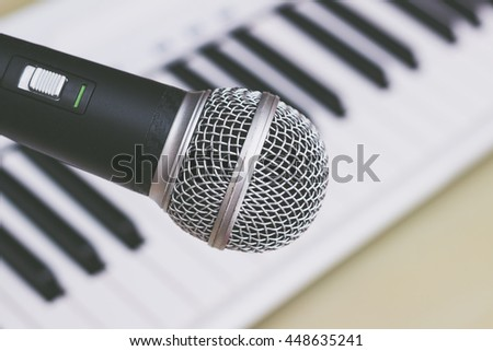 microphone on piano keys background, film filter