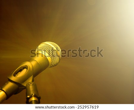 microphone on stage against golden rays - stock photo