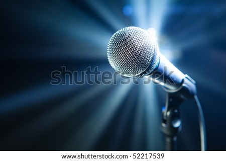microphone on stage with blue background - stock photo