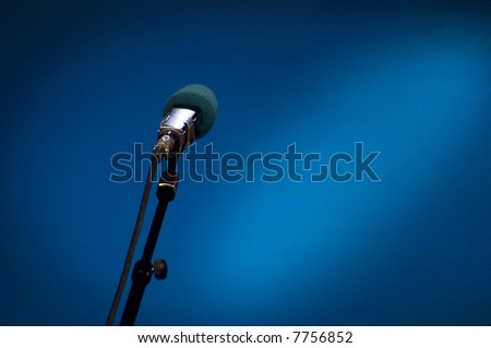 Microphone on stage with blue background and lights - stock photo