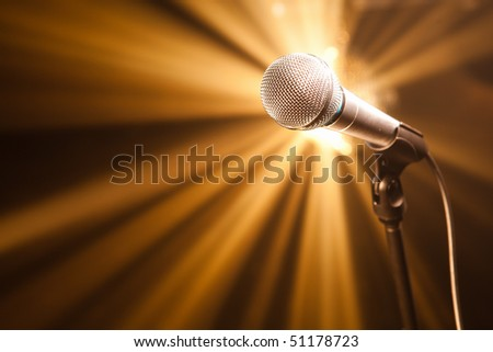 microphone on stage with golden rays - stock photo