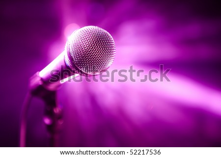microphone on stage with purple background - stock photo