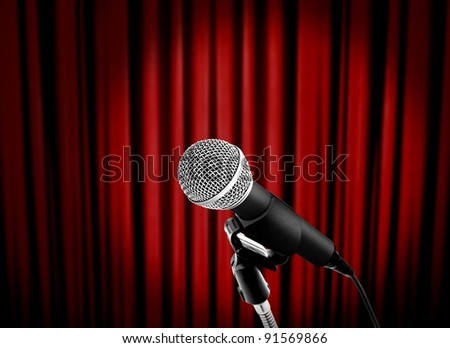 microphone on stage with red curtain - stock photo