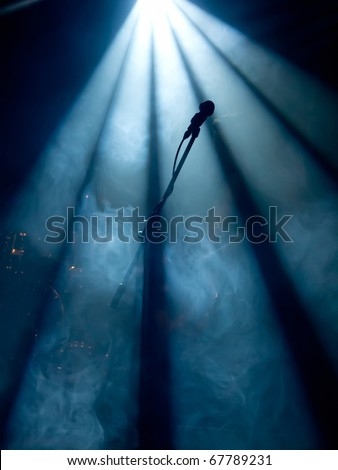 Microphone on stage with stage-lights in the background - stock photo