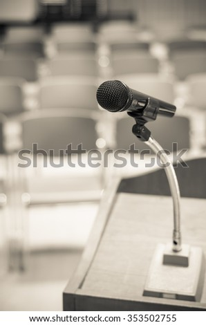 Microphone on the speech podium over the Abstract blurred photo of conference hall or seminar room background - stock photo