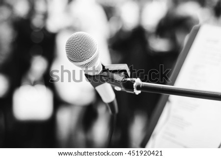 Microphone on the stand at the background of the crowd. Black and white photo.