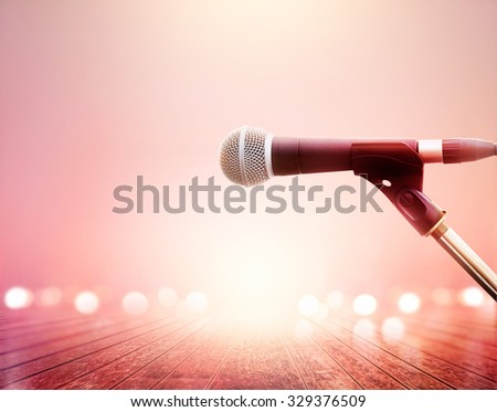 Microphone on vibrant lighting concert, wooden floor background, soft and blur  - stock photo