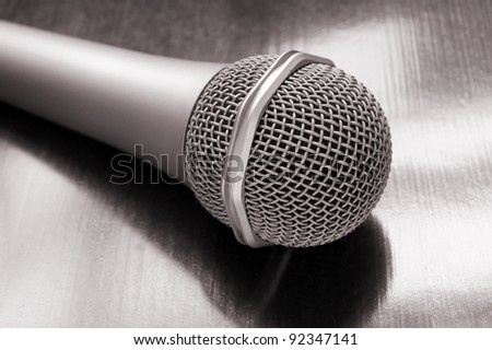 Microphone on wooden background close up