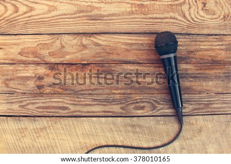 Microphone on wooden background. Toned image.  - stock photo