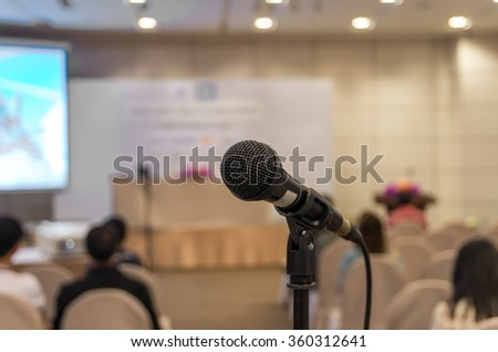 Microphone over the Abstract blurred photo of conference hall or seminar room background - stock photo