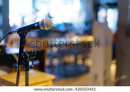 Microphone over the Abstract blurred photo of conference hall or seminar room background. - stock photo