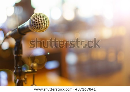 Microphone over the Abstract blurred photo of conference hall or seminar room background. Black and white - stock photo