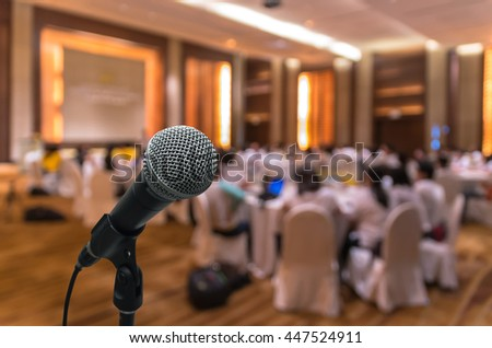 Microphone over the Abstract blurred photo of conference hall or seminar room with attendee background - stock photo