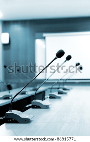 Microphone stands on meeting room table - stock photo
