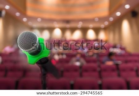 Microphone with Abstract blurred photo of conference hall or meeting room with attendee background