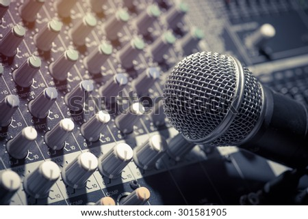 microphone with audio mixer, music equipment in vintage tone style - stock photo