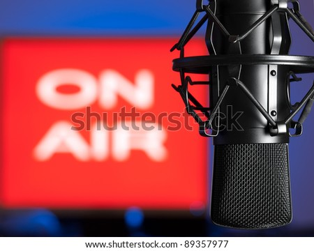 Microphone with blurred on  air sign in the background, for broadcasting,sound related themes - stock photo