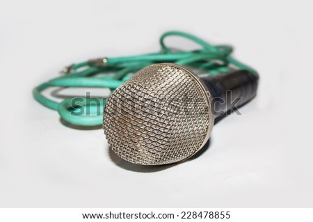 Microphone with green cable on light background - stock photo