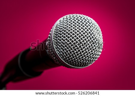 Microphone with metal body in holder, isolated on crimson background, close-up