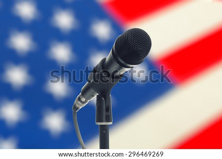 Microphone with US flag on background - studio shot - stock photo