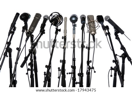 Microphones aligned together isolated over a white background - stock photo