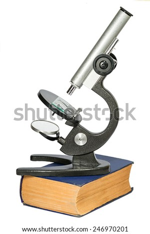 microscope standing on the thick old book isolated on white background - stock photo