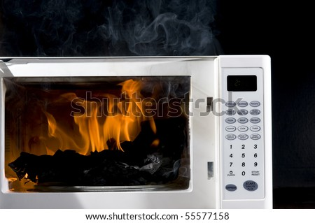 Microwave is broken filled hot flame - stock photo