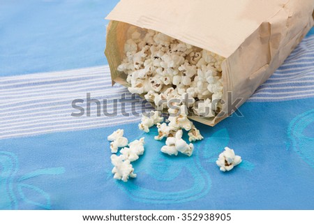 microwave popcorn, on traditional tablecloth - stock photo