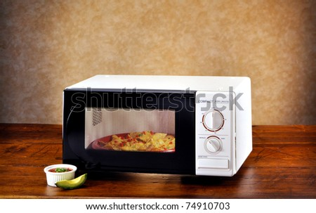 Microwave with nachos and avocado on wood set - stock photo