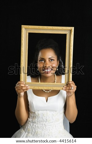 Mid-adult African-American bride holding frame around her face. - stock photo
