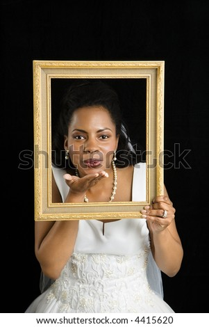 Mid-adult African-American bride holding frame around her face and blowing a kiss. - stock photo