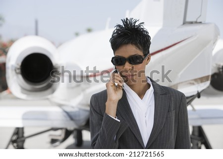 Mid-adult African-American businesswoman standing in front of private plane and talking on phone. - stock photo