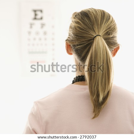 Mid-adult African-American doctor with clipboard and Caucasion mid-adult female patient in doctor's office looking at viewer and smiling. - stock photo