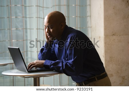 MId-adult African American male typing on laptop computer. - stock photo