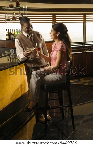 Mid adult African American man toasting Hispanic woman at bar. - stock photo