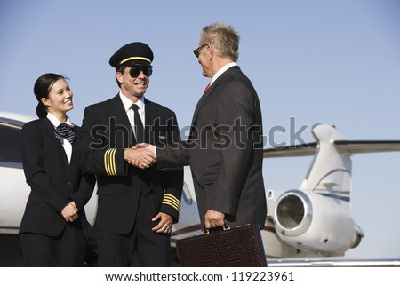 Mid-adult airline pilot and senior businessman shaking hands - stock photo