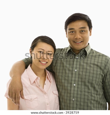 Mid adult Asian couple with arms around eachother smiling. - stock photo