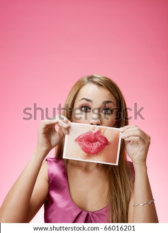mid adult blond woman holding photo of her mouth kissing on pink background. Horizontal shape, front view, head and shoulders, copy space - stock photo