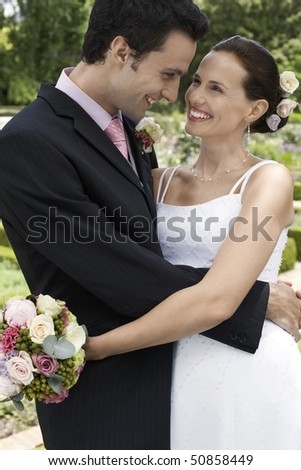 Mid adult bride and groom in garden, embracing