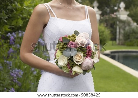 Mid adult bride at poolside, holding bouquet, mid section