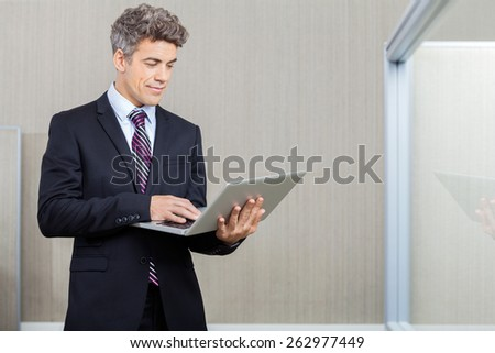 Mid adult business executive working on laptop at call center - stock photo